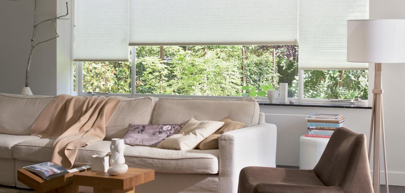 Modelo de cortina motorizada Duette na cor branca em sala com sofá, poltrona, abajur e livros