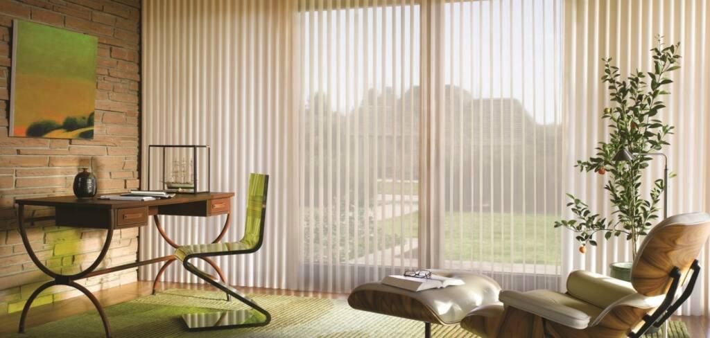 Modelo de persiana Luminette na cor branca em escritório moderno com mesa, cadeira, quadro na parede e poltrona com descanso para os pés