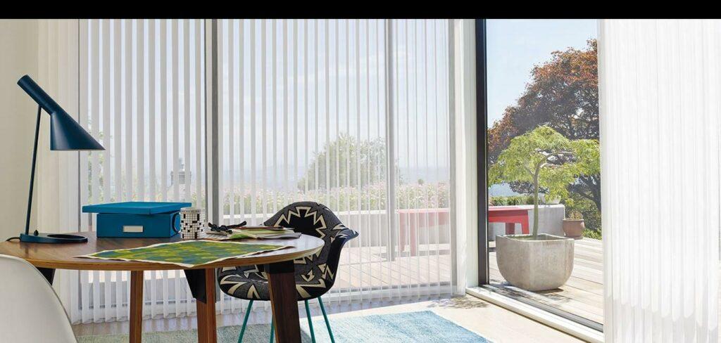 Modelo de persiana Luminette na cor branca em cômodo com cadeira, abajur e objetos em cima de mesa redonda de madeira com vista para área verde externa