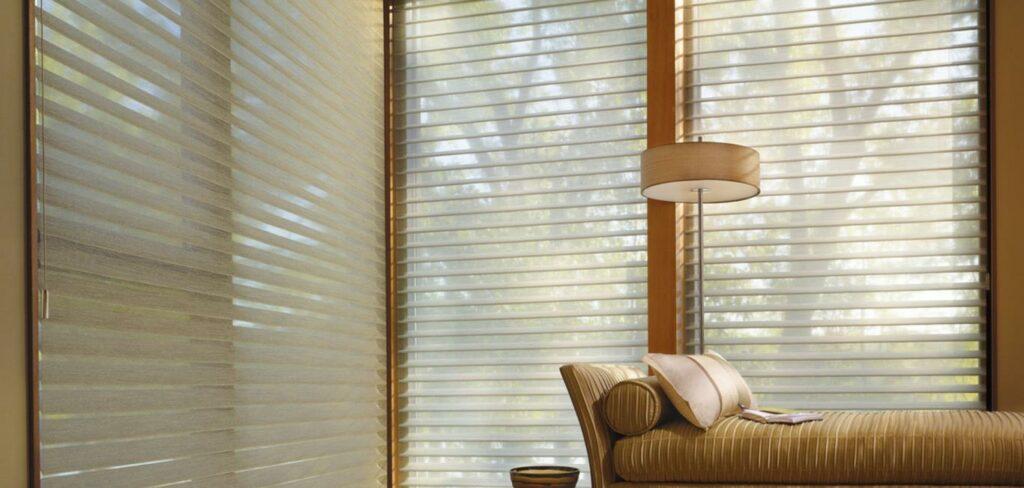 Modelo de persiana Silhouette na cor beje em cômodo com divã e abajur