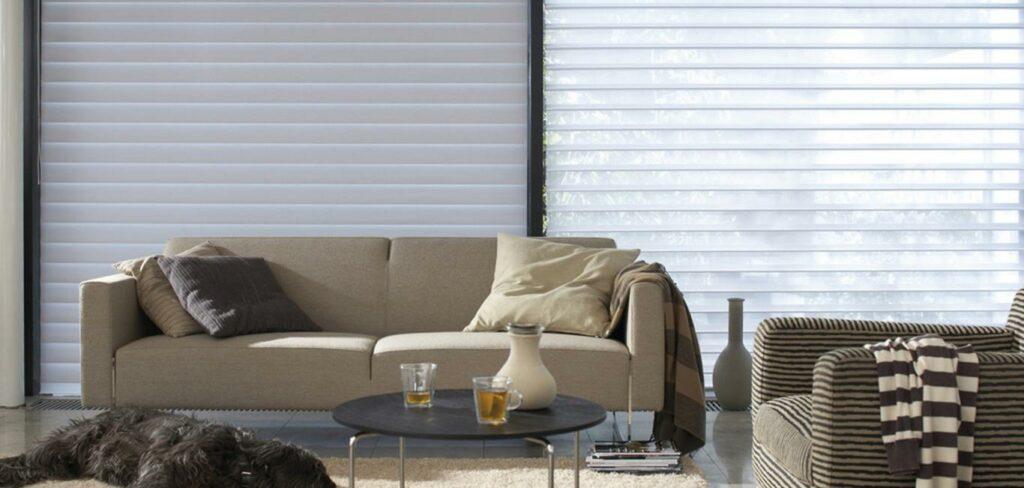 Modelo de persiana Silhouette na cor branca em sala com sofá, poltrona, mesa de centro e um cachorro preto deitado no tapete